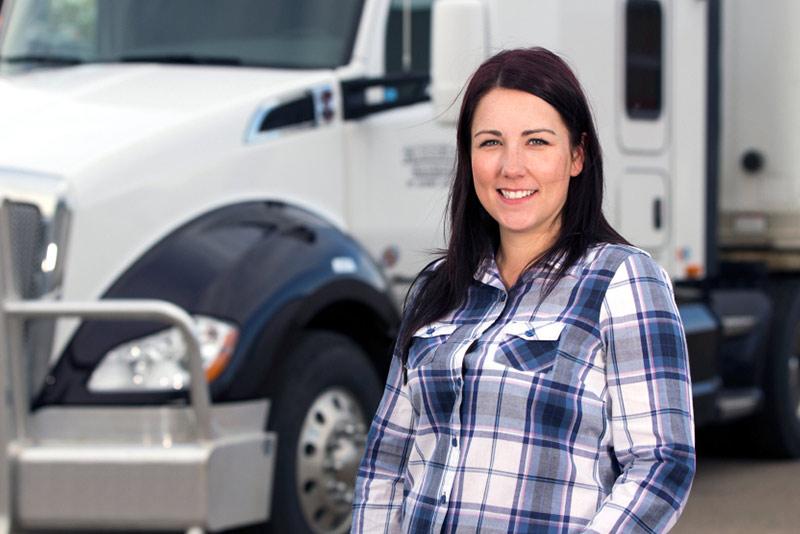 Mujer transportista frente a su camión Clase 8